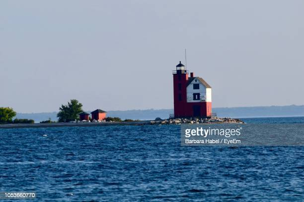 lighthouse by sea against clear sky - mackinac island stock pictures, royalty-free photos & images