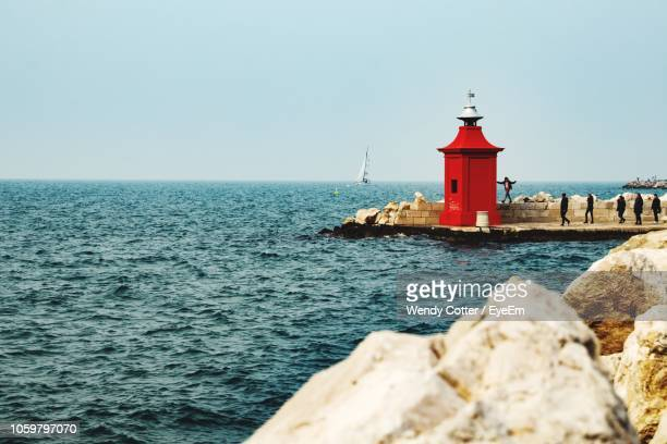 lighthouse by sea against clear sky - koper stock photos and pictures
