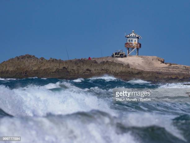 lighthouse by sea against clear sky - mogadishu stock photos and pictures