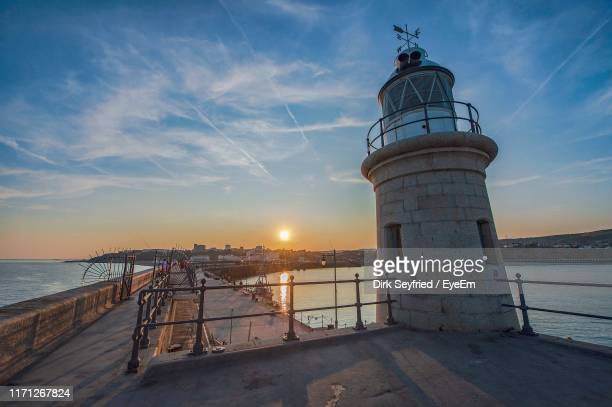 lighthouse by sea against sky during sunset - kent england stock pictures, royalty-free photos & images