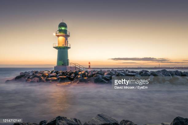 lighthouse by sea against sky during sunset - 防波堤 ストックフォトと画像