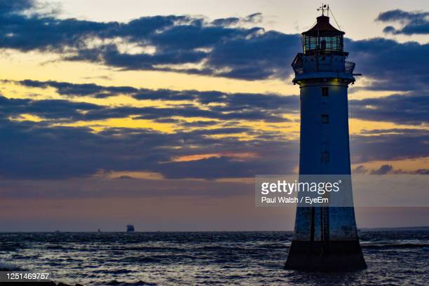 lighthouse by sea against sky during sunset - tower stock pictures, royalty-free photos & images