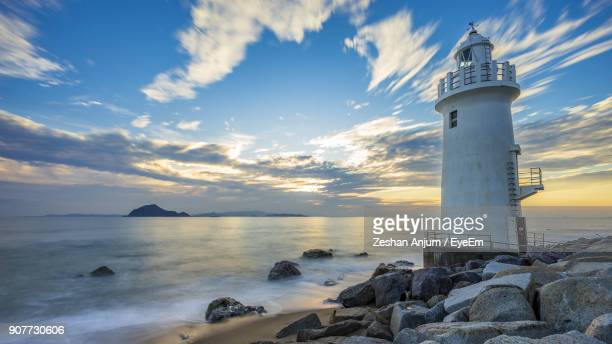 lighthouse by sea against sky during sunset - aichi prefecture stock pictures, royalty-free photos & images