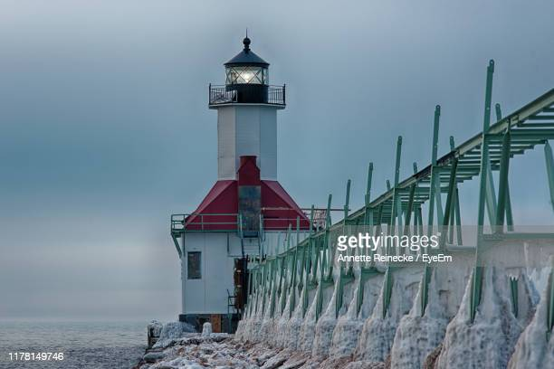 lighthouse by sea against sky during winter - annette haven foto e immagini stock