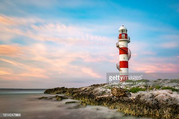 lighthouse by sea against sky - cancun stock photos and pictures