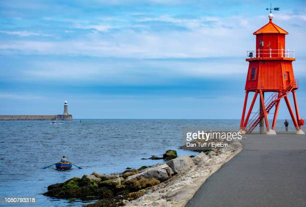 lighthouse by sea against sky - newcastle upon tyne stock pictures, royalty-free photos & images