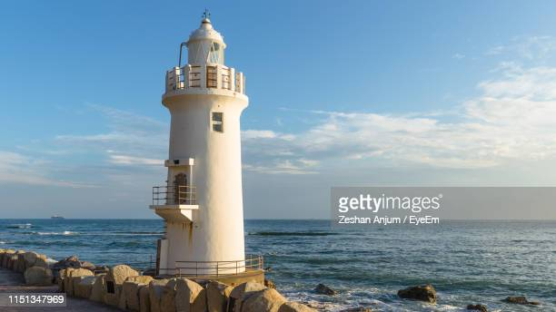 lighthouse by sea against sky - aichi prefecture stock pictures, royalty-free photos & images