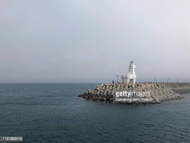 lighthouse by sea against sky - jeju - fotografias e filmes do acervo