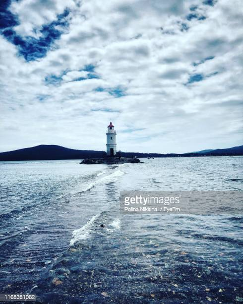 lighthouse by sea against sky - nikitina stock pictures, royalty-free photos & images