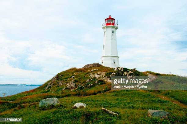 lighthouse by sea against sky - cape breton island stock pictures, royalty-free photos & images