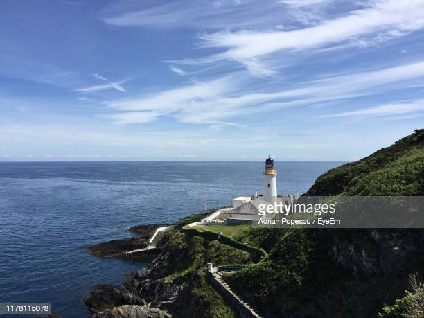 lighthouse by sea against sky - irish sea stock pictures, royalty-free photos & images