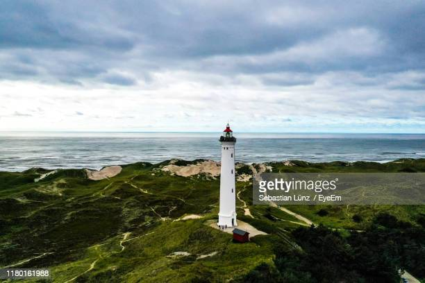 lighthouse by sea against sky - denmark stock pictures, royalty-free photos & images