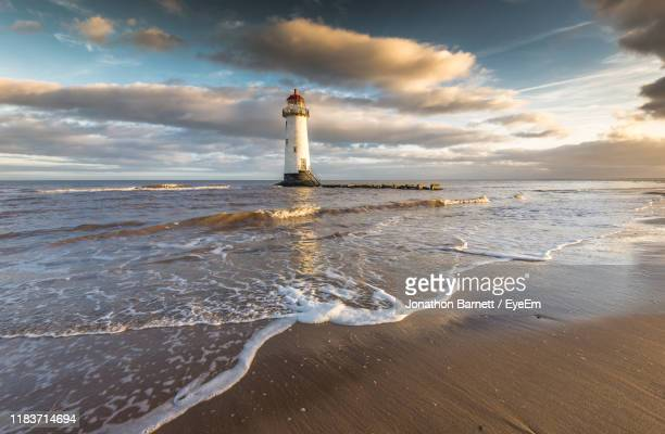 lighthouse by sea against sky - guidance stock pictures, royalty-free photos & images