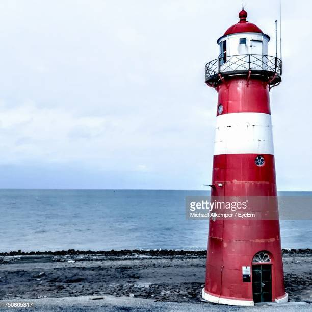 lighthouse by sea against sky - leuchtturm stock-fotos und bilder