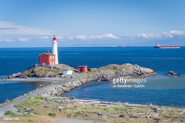 lighthouse by sea against sky - vancouver island stockfoto's en -beelden
