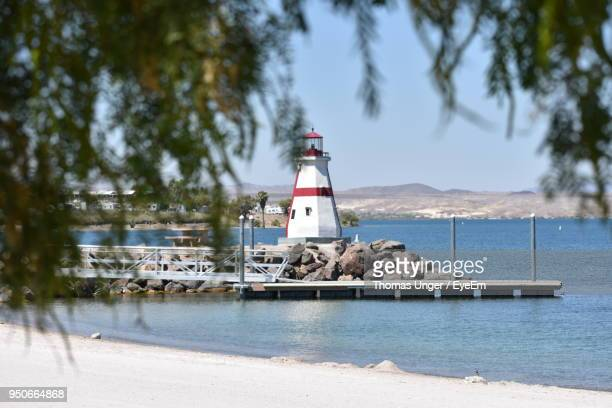 lighthouse by sea against sky - lake havasu stock photos and pictures