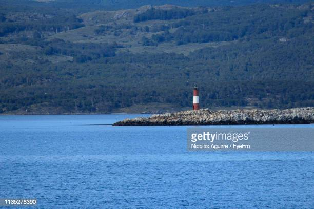 Lighthouse By Sea And Buildings Against Mountain