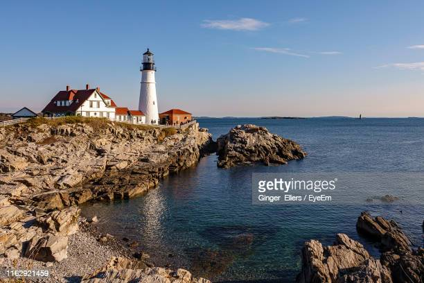 lighthouse by sea and buildings against sky - portland maine stock pictures, royalty-free photos & images