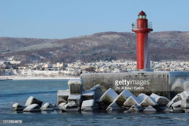 lighthouse by sea and buildings against sky - sea of okhotsk stock pictures, royalty-free photos & images