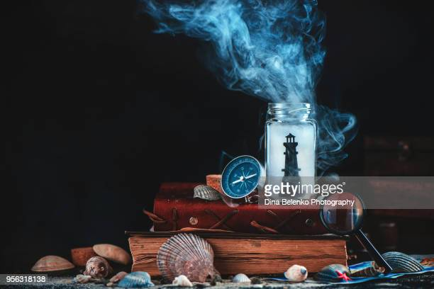 Lighthouse in a glass jar on a stack of books and captain logs. Sea still life with compass, globe and seashells on a dark background with smoke. Marine concept with copy space.