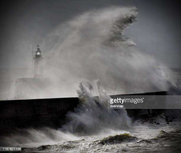 lighthouse in a storm - pier stock pictures, royalty-free photos & images