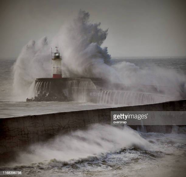 lighthouse in a storm - lighthouse stock pictures, royalty-free photos & images