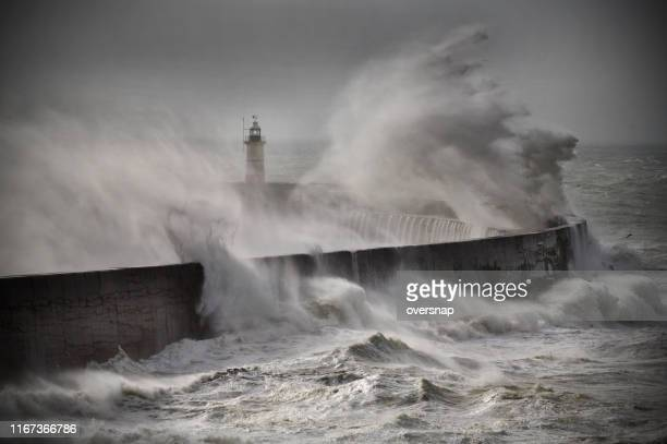 lighthouse in a tempest - climate change stock pictures, royalty-free photos & images