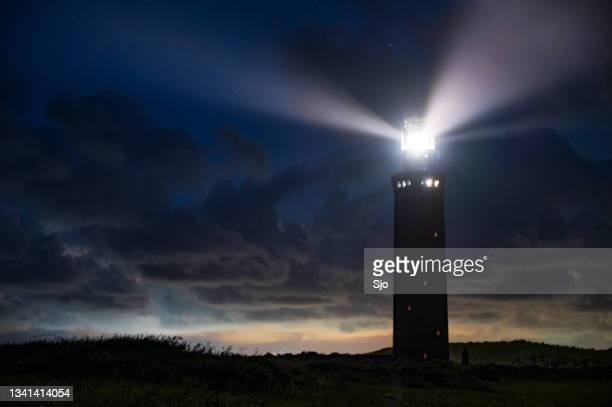 """lighthouse in the dunes with lightbeams at night - """"sjoerd van der wal"""" or """"sjo""""nature stockfoto's en -beelden"""