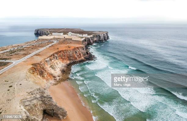 lighthouse in the middle of the land entering the sea with the waves breaking the coast - sagres stock pictures, royalty-free photos & images