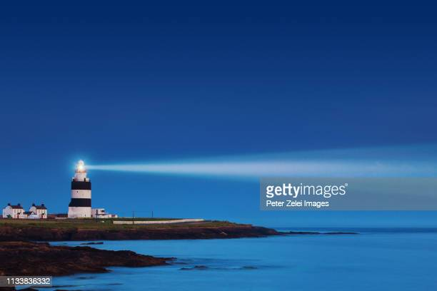 lighthouse in the night - lighthouse stock pictures, royalty-free photos & images