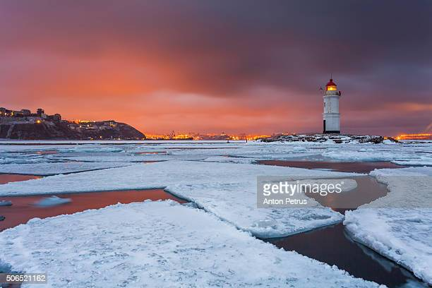 Lighthouse in winter sea at sunset