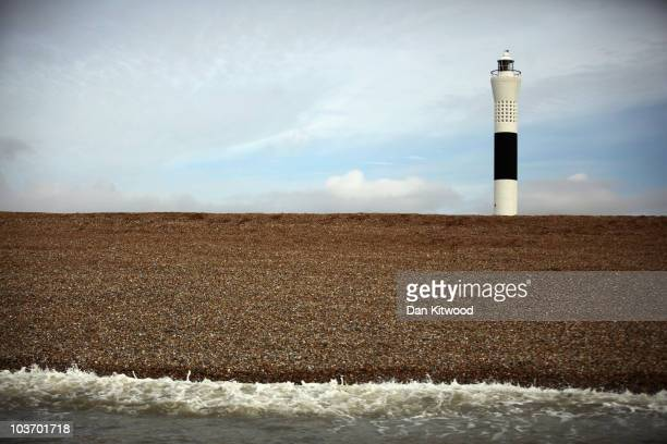 A lighthouse is pictured above the shingle on August 25 2010 in Dungeness England The Dungeness National Nature Reserve is a desolate landscape of...