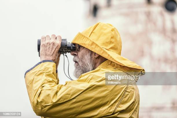 Lighthouse Keeper Looking Through Binoculars Near Lighthouse