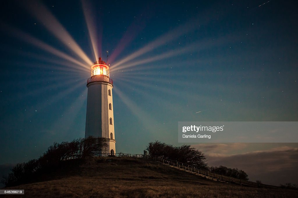 Lighthouse on a hill shining at night : Stock Photo