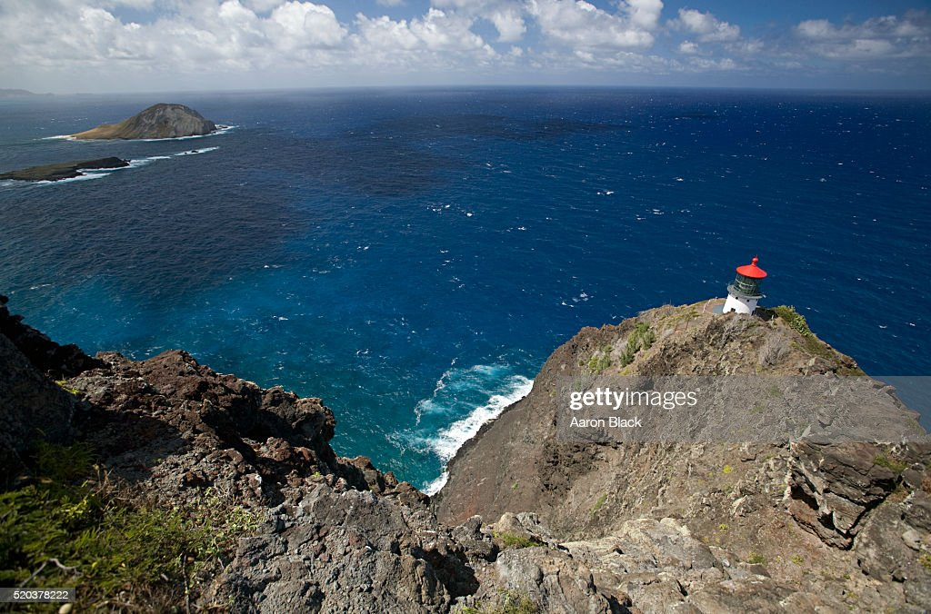 Lighthouse on a rocky outlook over the sea : Stock Photo