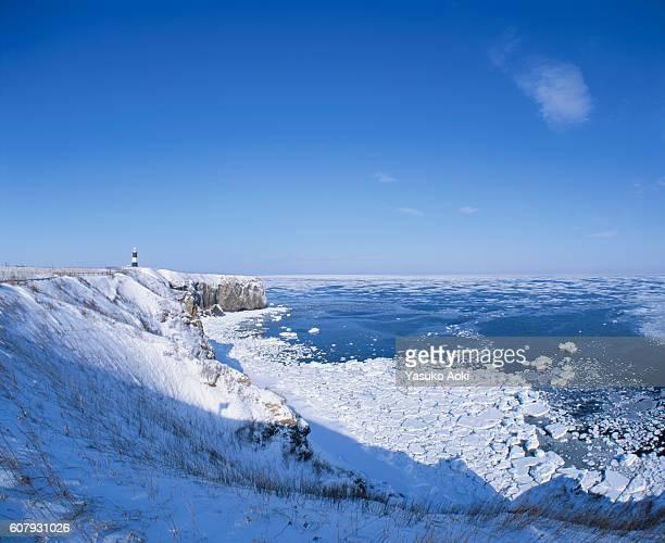 A Lighthouse on a Snowy Cliff Overlooking Drift Ice and the Ocean. Abashiri, Hokkaido, Japan