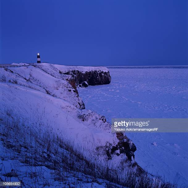 A Lighthouse on a Snowy Cliff Overlooking the Frozen Ocean. Hokkaido, Japan