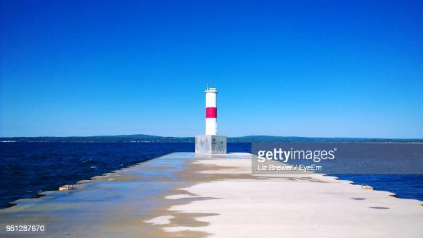 lighthouse on beach against clear blue sky - liz brewer stock photos and pictures