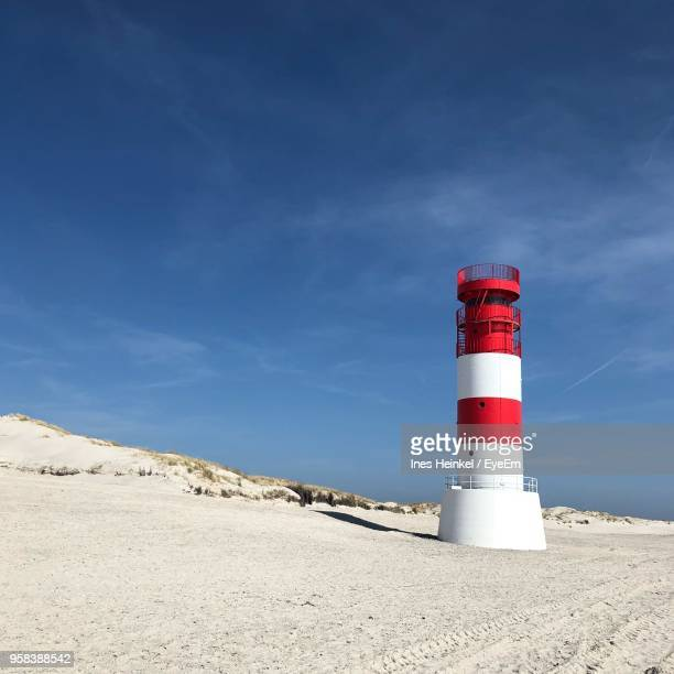 lighthouse on beach against sky - helgoland stock pictures, royalty-free photos & images