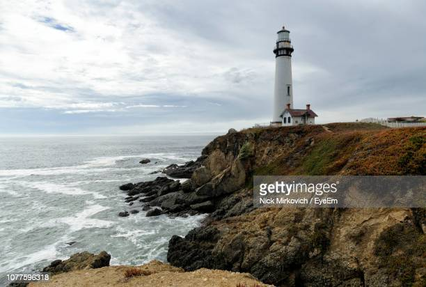 lighthouse on beach by sea against sky - san mateo county stock pictures, royalty-free photos & images