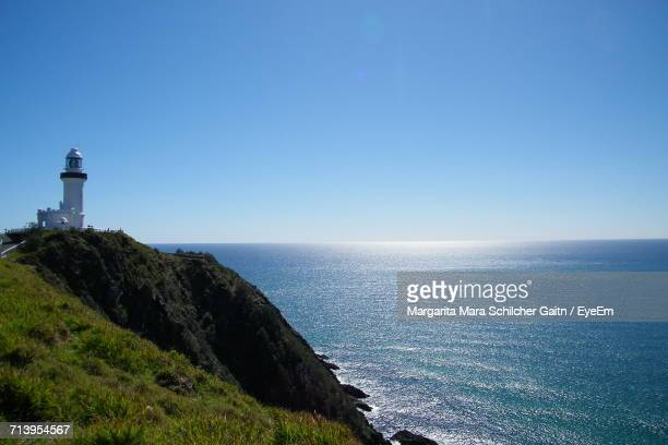 Lighthouse On Cliff By Sea Against Clear Blue Sky