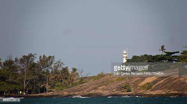 lighthouse on cliff by sea against clear sky - filho stock-fotos und bilder