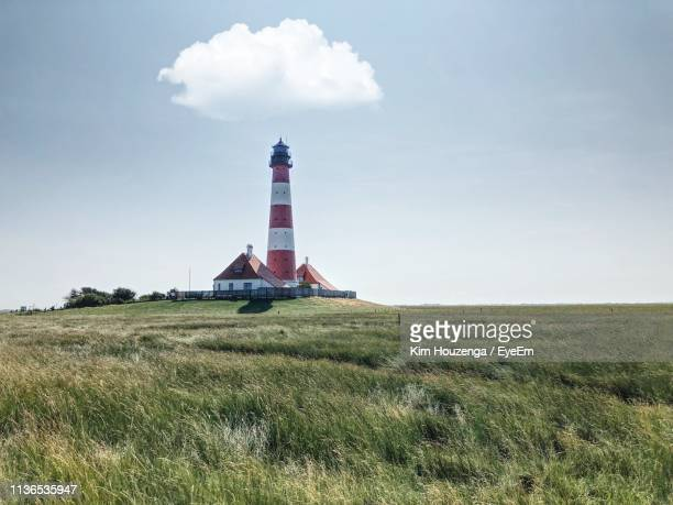 lighthouse on field against sky - schleswig holstein stock pictures, royalty-free photos & images