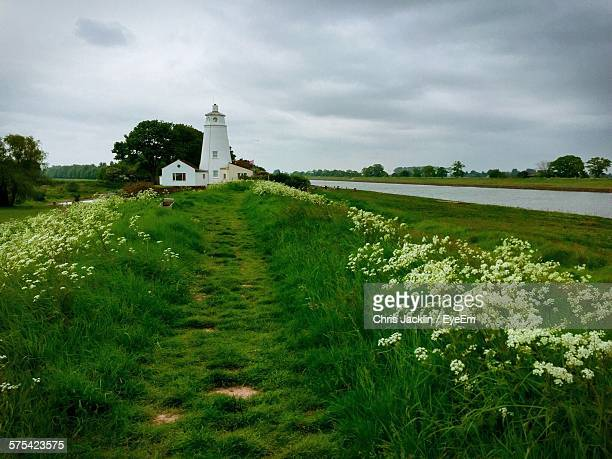 lighthouse on field by river against cloudy sky - lincolnshire stock pictures, royalty-free photos & images