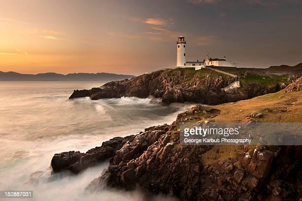 Lighthouse on foggy coastline