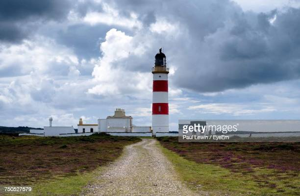 Lighthouse On Landscape Against Sky
