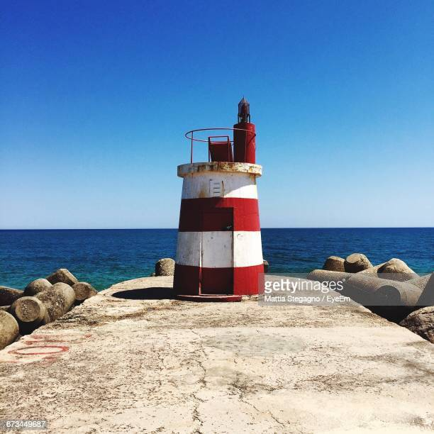 Lighthouse On Pier Against Clear Blue Sky