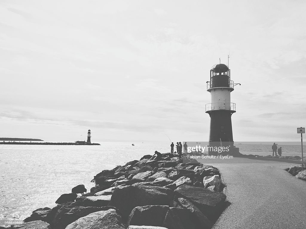 Lighthouse On Pier At Sea Against Sky : Stock Photo