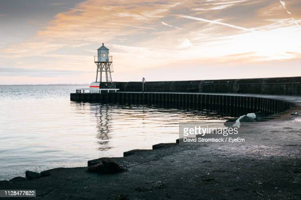 lighthouse on pier by sea against sky during sunset - helsingborg stock pictures, royalty-free photos & images