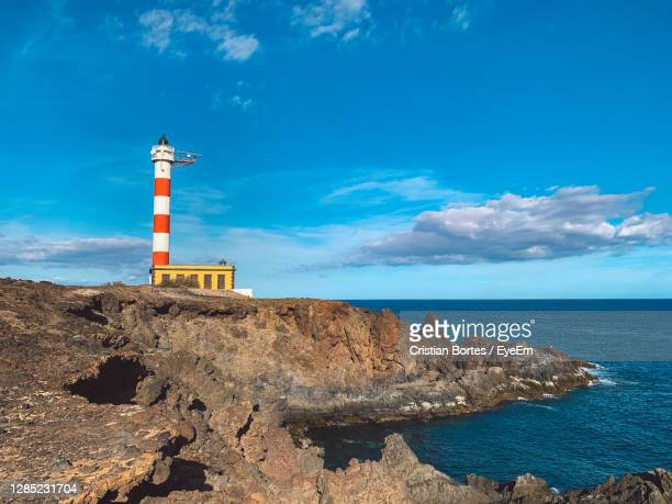 lighthouse on rock by sea against blue sky - bortes stock pictures, royalty-free photos & images